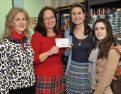 Alyson Novick, director of development for MLK Community Center holds a check presented to her by Salve Regina business students Erica Smith and Caitlin Seidl, along with their advisor, Dr. Arlene Nicholas.